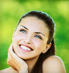 woman with bare shoulders laughs and looks up